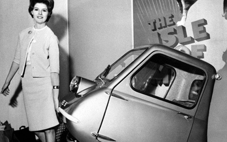 mulher levantando o menor carro do mundo